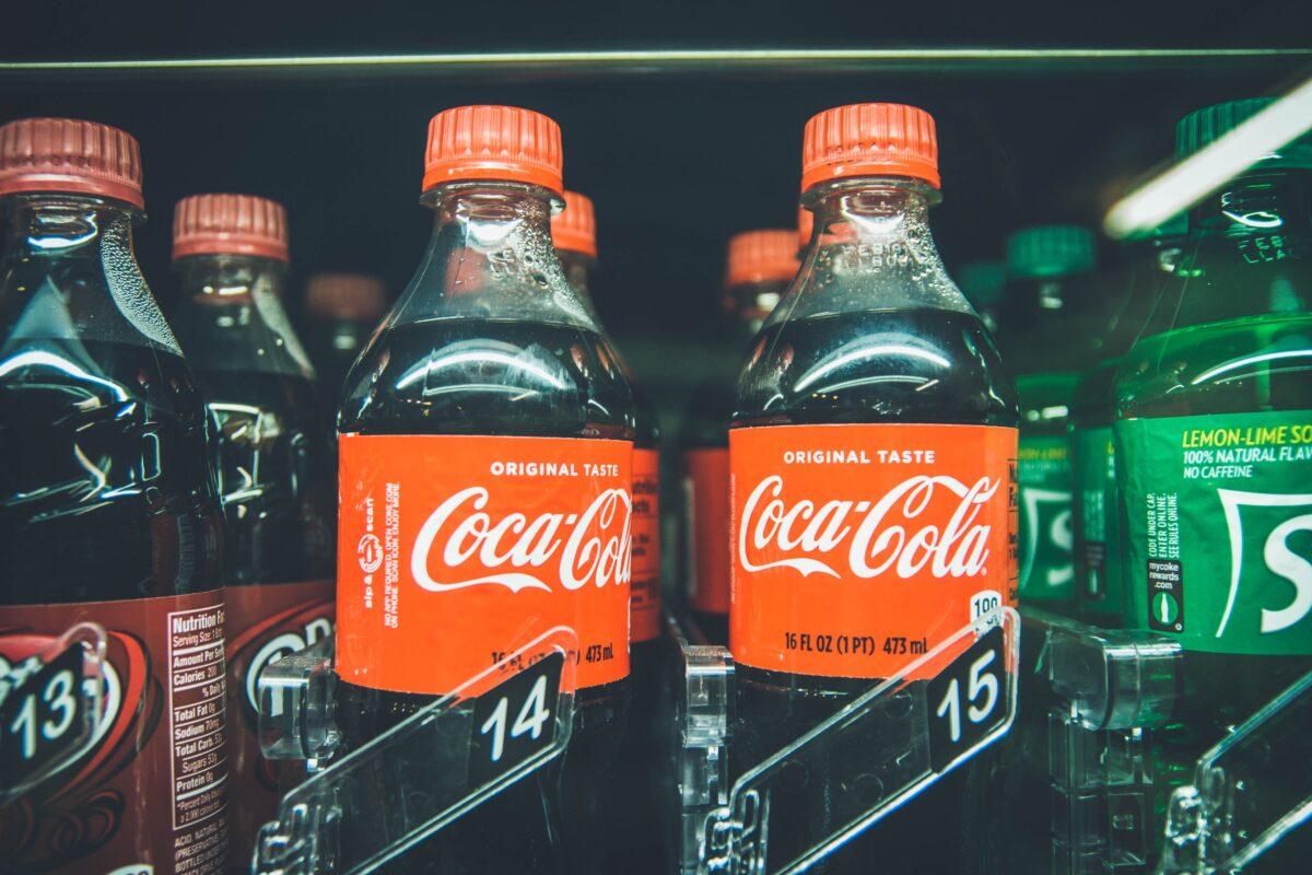 Coca-Cola bottles in between Sprite and another bottle
