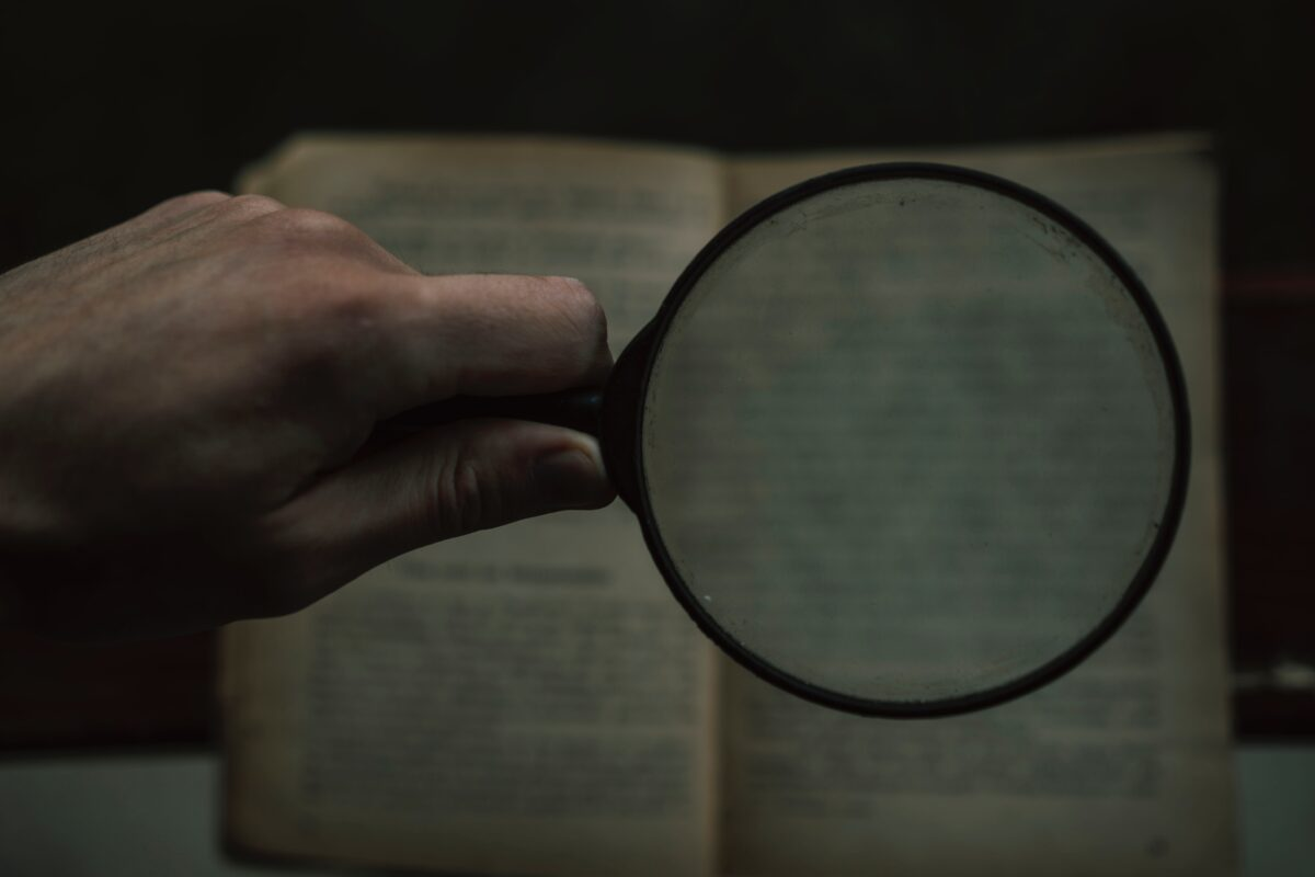 person holding magnifying glass with black frame